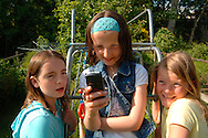 three young friends texting on the climbing frame