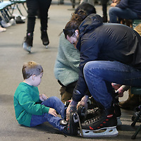 Chase Hubbard ties the ice skates of Oliver Stone, 5, Saturday at the Bancorpsouth Arena