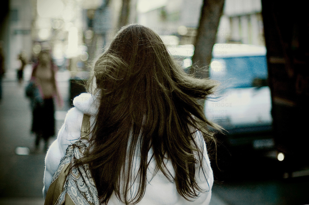 A young woman with long dark hair walking along a street