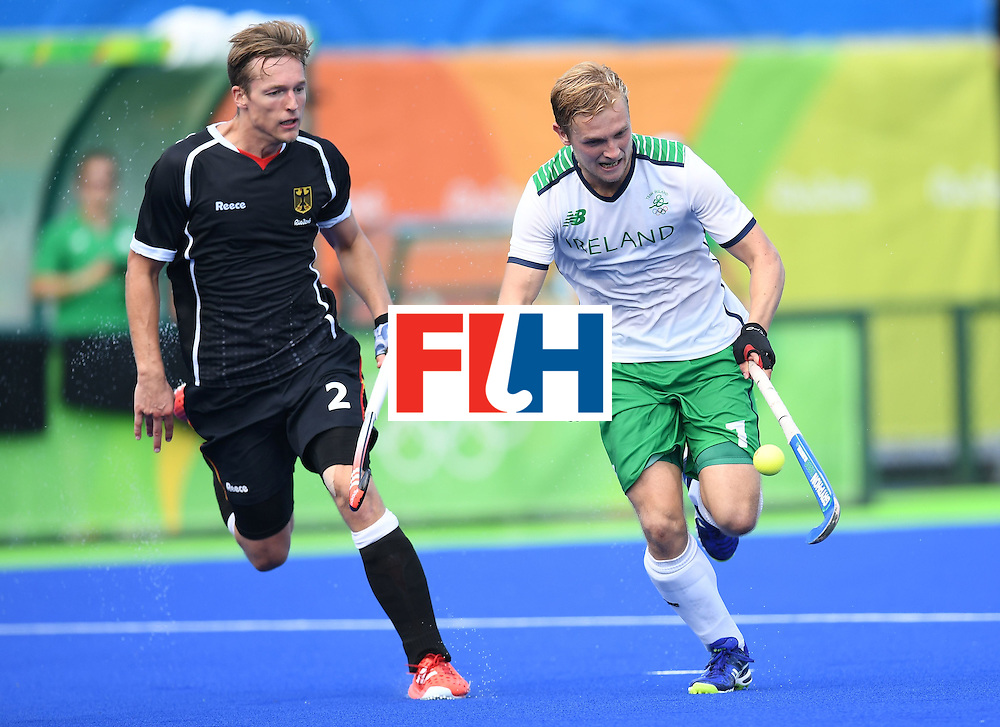 Ireland's Michael Watt(R) controls the ball as Germany's Mathias Muller chases during the men's field hockey Germany vs Ireland match of the Rio 2016 Olympics Games at the Olympic Hockey Centre in Rio de Janeiro on August, 9 2016. / AFP / MANAN VATSYAYANA        (Photo credit should read MANAN VATSYAYANA/AFP/Getty Images)