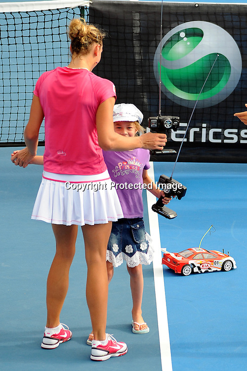 Yanian Wickmayer with KIA remote control car racing a little girl at the WTA 2011 ASB Classic, ASB Tennis Centre, Auckland, New Zealand. Wednesday 5 January 2011. Photo: Chris Symes/photosport.co.nz