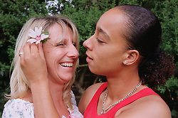 Woman placing flower in partner's hair,
