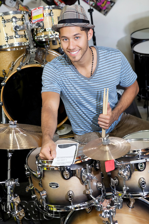 Portrait of a young customer with drum set in music store