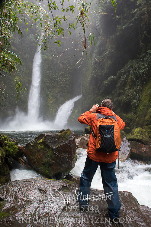 A hiker stops to take a photo of a waterfall at Pumalin National Park, Chile.