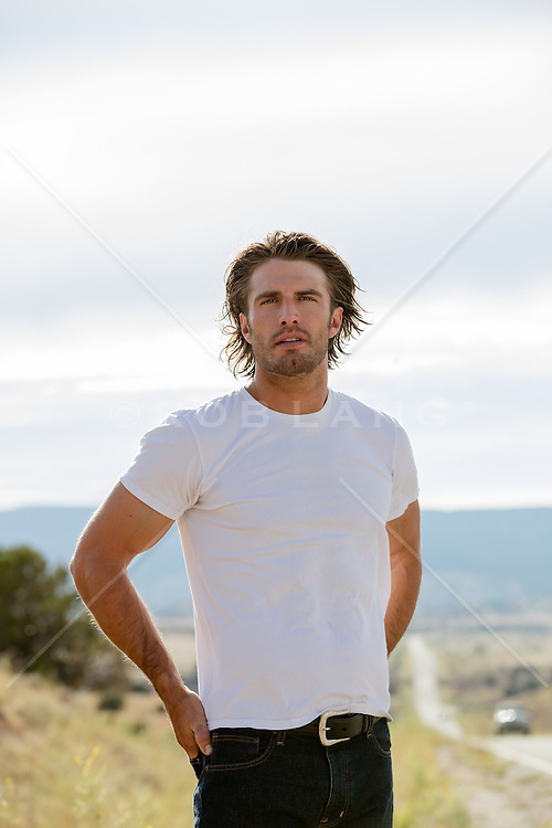 rugged man with long hair standing by a highway