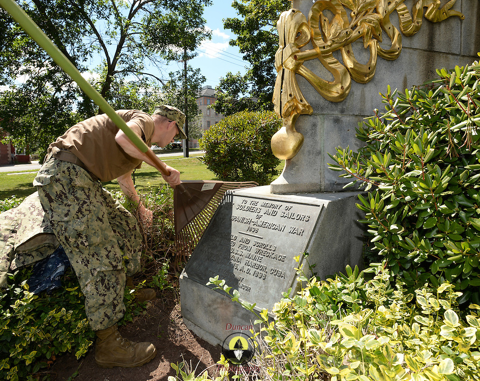 BANGOR Maine,  -- 8/8/15 - Builder 2nd Class Joshua Phillips of Gardiner, Maine refurbishes the landscaping at the USS Maine (ACR 1) Memorial in downtown Bangor on Saturday. Phillips, and four fellow reservists from Navy Operational Support Center, Bangor, spent the afternoon spreading mulch around the memorial's pathways. USS Maine, an armored cruiser commissioned in 1895, sank in Havana harbor in 1898, just prior to the Spanish-American War. (U.S. Navy Photo by Chief Mass Communication Specialist Roger S. Duncan/ Released)
