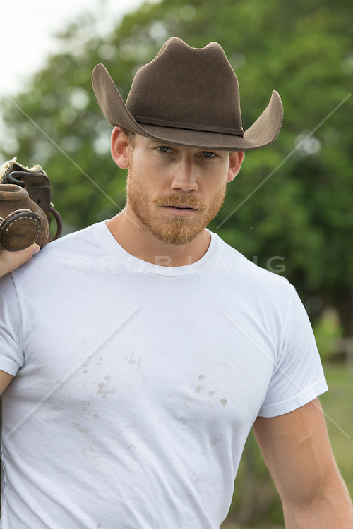 cowboy outdoors with a saddle