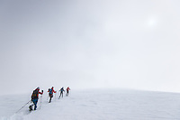 A team of mountaineers as seen during a long traverse of Glacier Blanche on a cold and misty Winter day.