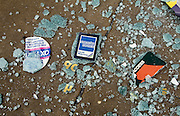 As if about to be crunched underfoot, shattered glass from the windows of offices in the historic City of London side-street, stickers and notices for Access (Mastercard) and American Express (Amex) credit cards lie on the disaster-strewn pavement (sidewalk). This is some of the debris lying about after the huge Bishopsgate bomb on 24th April 1993, London's most expensive terrorist atrocity during the Provisional Irish Republican Army's (IRA) sustained bombings on the British mainland. Buildings up to 500 metres away were damaged, with one and a half million square feet (140,000 sq m) of office space being affected and over 500 tonnes of glass broken. Costs of repairing the damage was estimated at £350 million and was possibly the IRA's most successful military tactic since the start of what was called the Troubles from 1969 onwards.