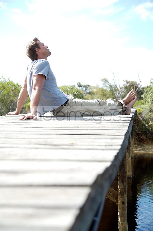 Portrait of barefoot man sitting on a boardwalk by a river