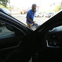 After a wash and dry Jerry Montgomery begins putting on the wax as part of the detailing job at Traylor's Detail Shop on North Gloster.