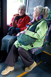 Two friends sitting on the bus chatting,