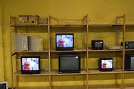 """gebruikte televiesieapparatuur in een stellingkast bij kringloopwinkel """"het Goed"""" aan de Lonnekerbrugstraat in enschede vertoont een aflevering van sesamstraat"""