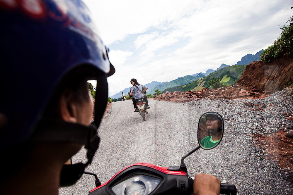 Motorbike riders drive on a side road winding along the mountains of Son La Province, Vietnam, Southeast Asia
