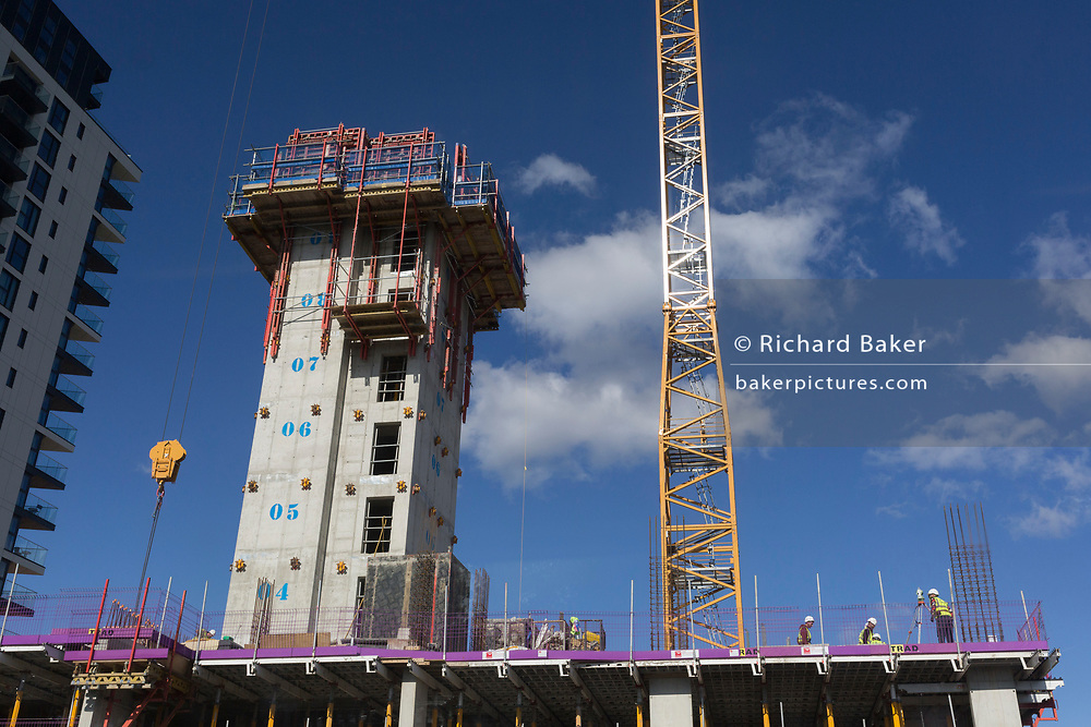 Construction workers beneath a crane and lift shaft, survey a new building complex, on 2nd October 2019, in Sutton, London, England.