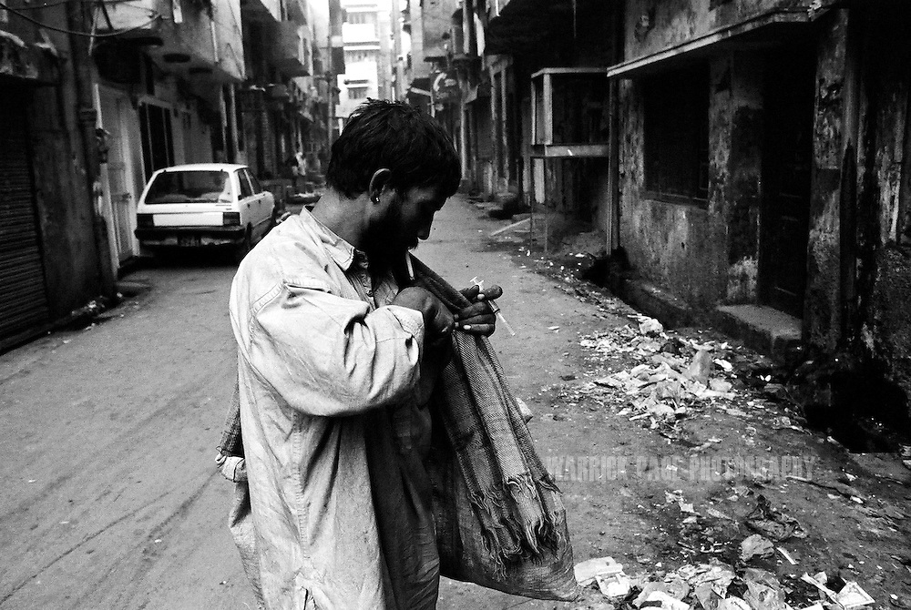 A heroin user prepares to inject in the streets of Lahore's Old City, December 11, 2004, Lahore, Pakistan. Pakistan is one of the major transit points for Afghanistan's heroin trade. Heroin is cheap and readily available in Pakistan due to it's proximity to Afghanistan which supplies almost 90% of heroin to Europe, December 11, 2004, Lahore, Pakistan. Almost 20% of heroin produced in Afghanistan is trafficked through Pakistan according to the UN Office on Drugs and Crime (UNODC). With the fall of the Taliban, opium cultivation has risen dramatically in spite of Afghan and coalition forces attempts to stem production. Pakistan has between 3.5-4 million heroin users, one of the highest numbers of heroin users in the world, next to Iran. (Photo by Warrick Page)