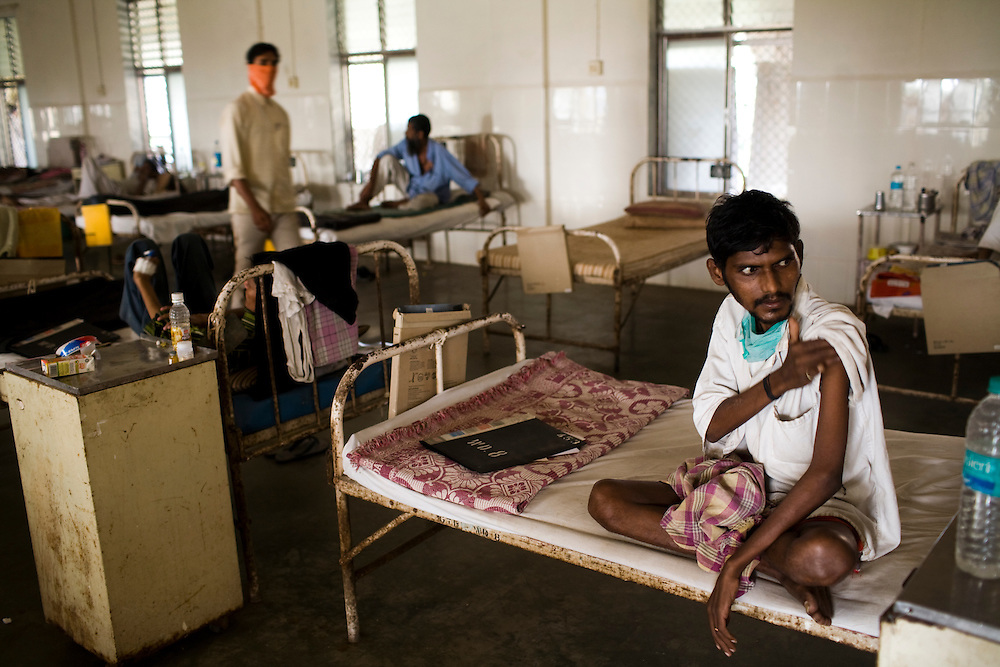 A patient sits on his bed after receiving an injection at the Group of TB Hospitals in Mumbai, India.