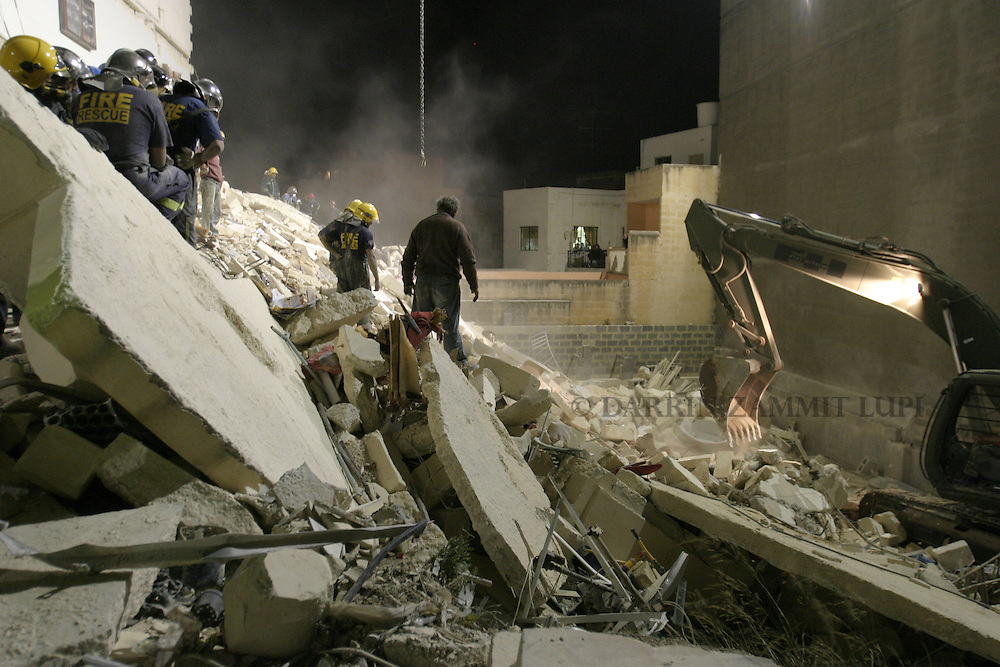 Civil Protection officers wait for a treacherous area of rubble to be gently cleared by a mechanical  shovel during a search and rescue operation where an apartment block collapsed leaving two women, one Maltese and one Russian, dead in the village of St Paul's Bay in the north of Malta early June 4, 2004.   The building collapsed because of excavation works taking place on a site adjacent to it. ..MALTA OUT..REUTERS/Darrin Zammit Lupi