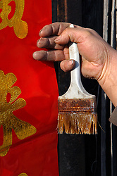 China, Taiyuan, 2007. A worker puts up traditional blessings on Lunar New Year's Eve. Doorways and entrances are considered good places for messages about luck and protection.