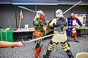 Anaheim , California - April 11, 2015: Two Lamia Knights Sir William Becking, in red, and Sir Adam Larios, in silver, perform a short bout during MicroCon 2015 at the Anaheim Central Library Saturday April 11, 2015. The Lamia Knights are a competitive medieval combat club based out of Hemet, CA, and the official sports team of Shiloh -- a micronation &quot;landlocked by Scotland,&quot; but ruled by Timothy Miller and his daughter Princess Samantha from Anaheim. Lord Jason Michael Wilson, background, keeps the fighting knights away from spectators and MicroCon displays.<br /> <br /> MicroCon 2015 is a Micronation conference held at the Anaheim Central Library.<br /> <br /> CREDIT: Matt Roth