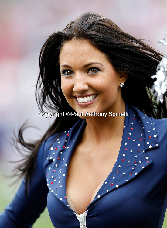A New England Patriots cheerleader waves her pom poms and smiles during a dance routine at the NFL regular season week 3 football game against the Buffalo Bills on September 26, 2010 in Foxborough, Massachusetts. The Patriots won the game 38-30. (©Paul Anthony Spinelli)
