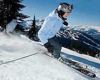 Woman (35-45) skiing on Blackcomb Mountain, Whistler, BC CANADA with Whistler Mountain behind.
