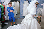A bride-to-be tries on her white wedding dress during a fiting in a London bridal shop.