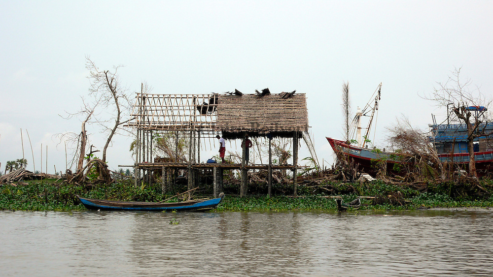 Fishermen rebuilding their house in the aftermath of Cyclone Nargis. Most of the villagers in this region are farmers or fishermen and they lost their boats and their paddy fields, their only livelihood.