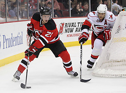 Feb 16; Newark, NJ, USA; New Jersey Devils left wing Mattias Tedenby (21) skates with the puck past Carolina Hurricanes defenseman Tim Gleason (6) during the second period at the Prudential Center.