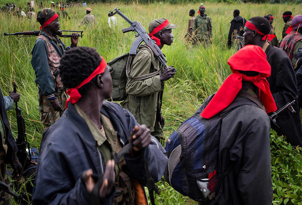 SPLA-IO (SPLA-In Opposition) rebels carry guns in Yondu, the day before an assault on government SPLA (Sudan People's Liberation Army) soldiers in the town of Kaya, on the border with Uganda, South Sudan.