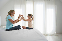 Mother and  daughter sitting on bed playing patty cake side view