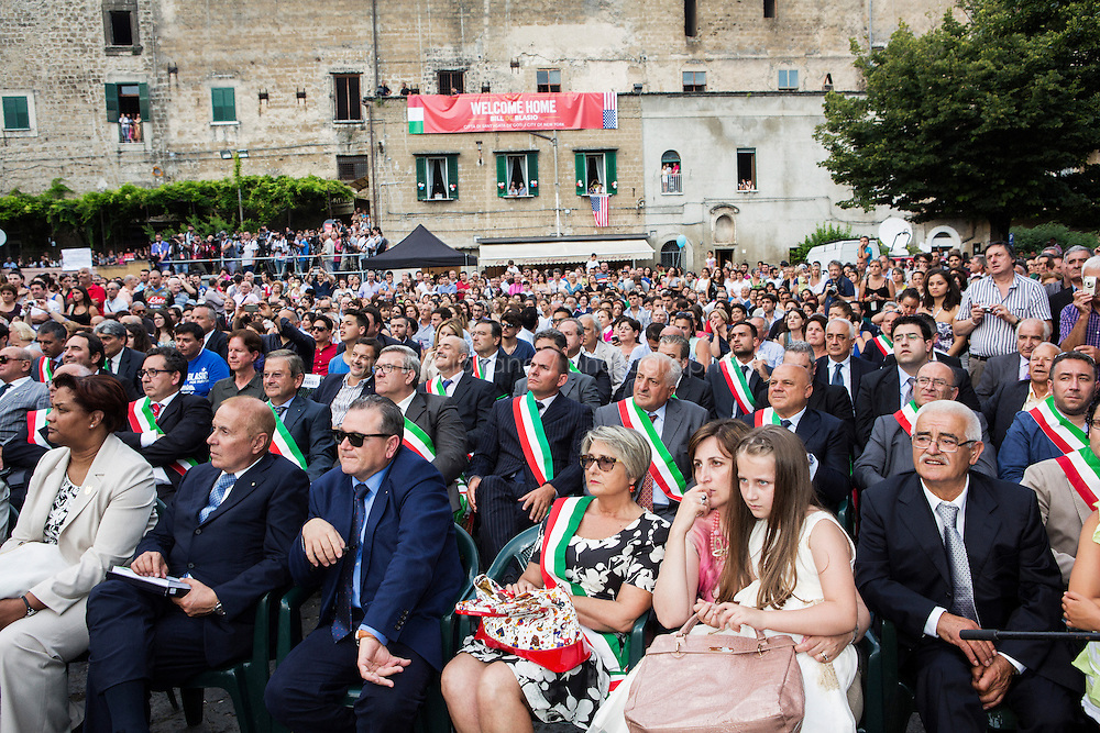 SANT'AGATA DE GOTI, ITALY - 23 JULY 2014: Mayors of the province of Benevento (in the first three rows, wearing an Italian mayotal sashes) and local residents listen to the speeches of local officials introducing Mayor of New York Bill De Blasio before giving him a honorary citizenship of Sant'Agata de Goti, the ancestral home town where Mr De Blasio is originally from, in Italy on July 23rd 2014.<br /> <br /> New York City Mayor Bill de Blasio arrived in Italy with his family Sunday morning for an 8-day summer vacation that includes meetings with government officials and sightseeing in his ancestral homeland.