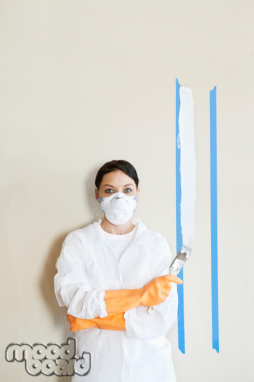 Portrait of female worker in protective workwear holding paint brush