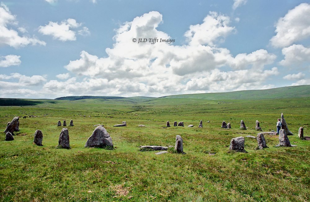 A vast, bright sky over Dartmoor reveals an ancient stone circle on the grassy moor.  The stones are only two to three feet high with a few taller exceptions, but the intentional circle is totally clear.  A young man leans against one of the taller stones, and a moorland pony is just visible in the distance.