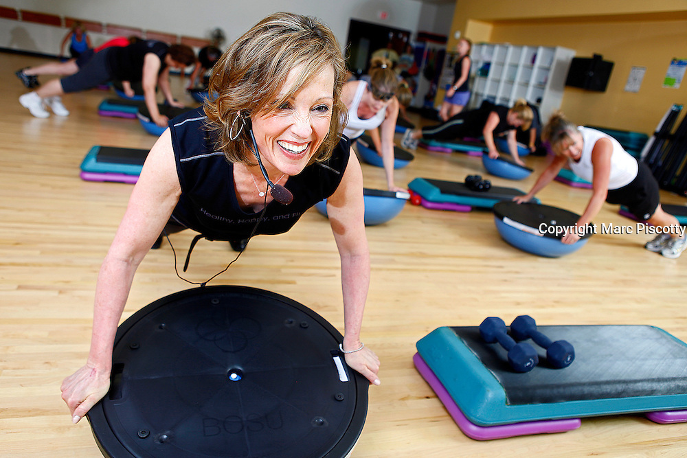 """8/19/10 5:26:13 PM -- Colorado Springs, CO. -- Margaret Sabin (left) the CEO of Penrose-St. Francis Hospital in Colorado Springs, Co. leads a """"Boot Camp"""" class at the hospital that combines aerobic activity, weight training and stretching. Sabin believes in practicing what they preach at the hospital in terms of leading a healthy lifestyle and has a number of employees buying in with some in the class losing as much as 90 pounds through the class. Sabin was a full-time aerobics teacher and currently teaches three different classes at the hospital. She has been the CEO at Penrose-St. Francis for about two years now. (Photo by Marc Piscotty/ © 2010)."""