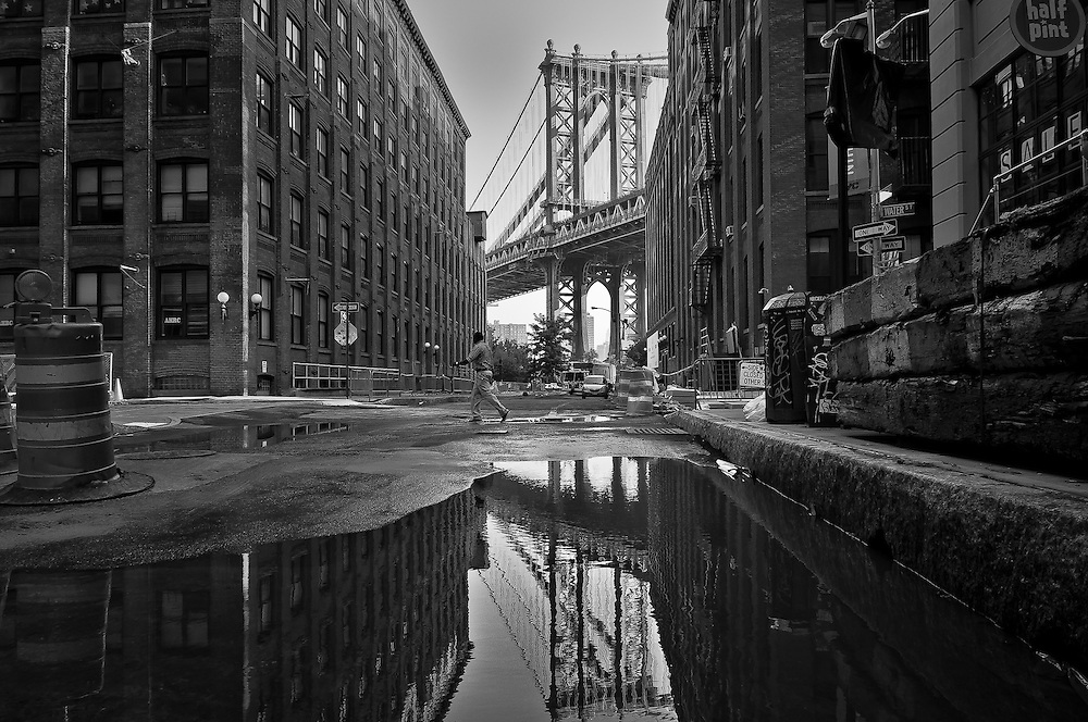 Reflection of the Manhattan Bride in a puddle on Washington Street in DUMBO, Brooklyn, New York