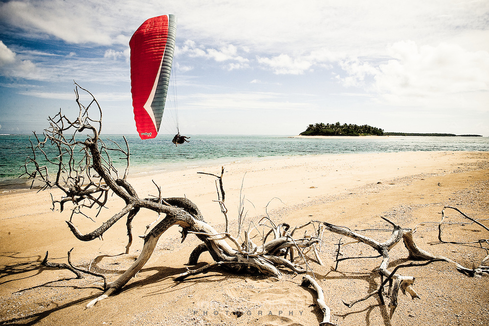 Professional paraglider Stu Belbas glides down onto a desserted beach in Tonga, South Pacific.  We were the first people to ever paraglide in the Kingdom, using our tow winch to reach heights of 1000 meters.