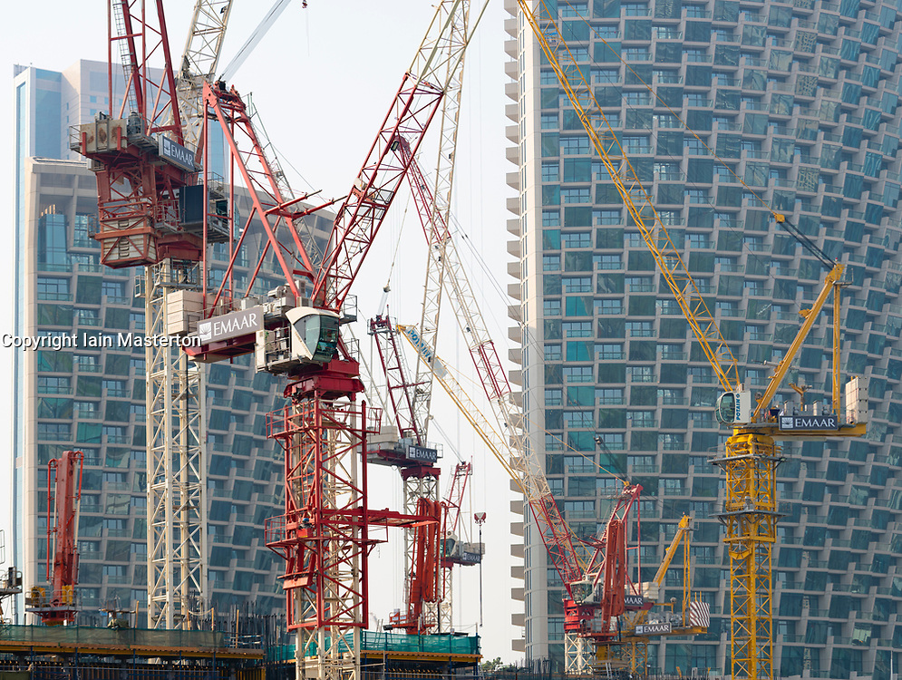 Many construction cranes on construction site building new high rise apartment towers in Downtown Dubai, UAE, United Arab Emirates,