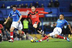 Wayne Rooney of Manchester United is tackled by Younes Kaboul of Portsmouth. Portsmouth v Manchester United (1-4), Barclays Premier League Fratton Park, Portsmouth, 28th November 2009.