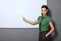 Portrait of businesswoman with hands in pockets pointing at whiteboard in office