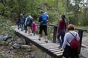 Polish families descend a rocky mountain footpath towards the village of Jaworki, on 21st September 2019, near Szczawnica, Malopolska, Poland.