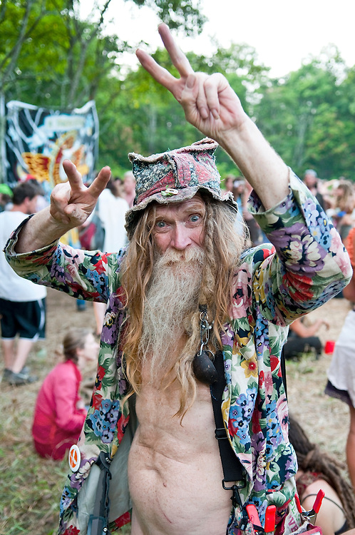 An old hippie, known as Grandpa Woodstock to younger folks, gives a two-handed peace sign at the annual Rainbow Gathering, which in 2012 was held in the Cherokee National Forest near Bristol, Tennessee. Photo taken in a meadow where participants had gathered for dinner.