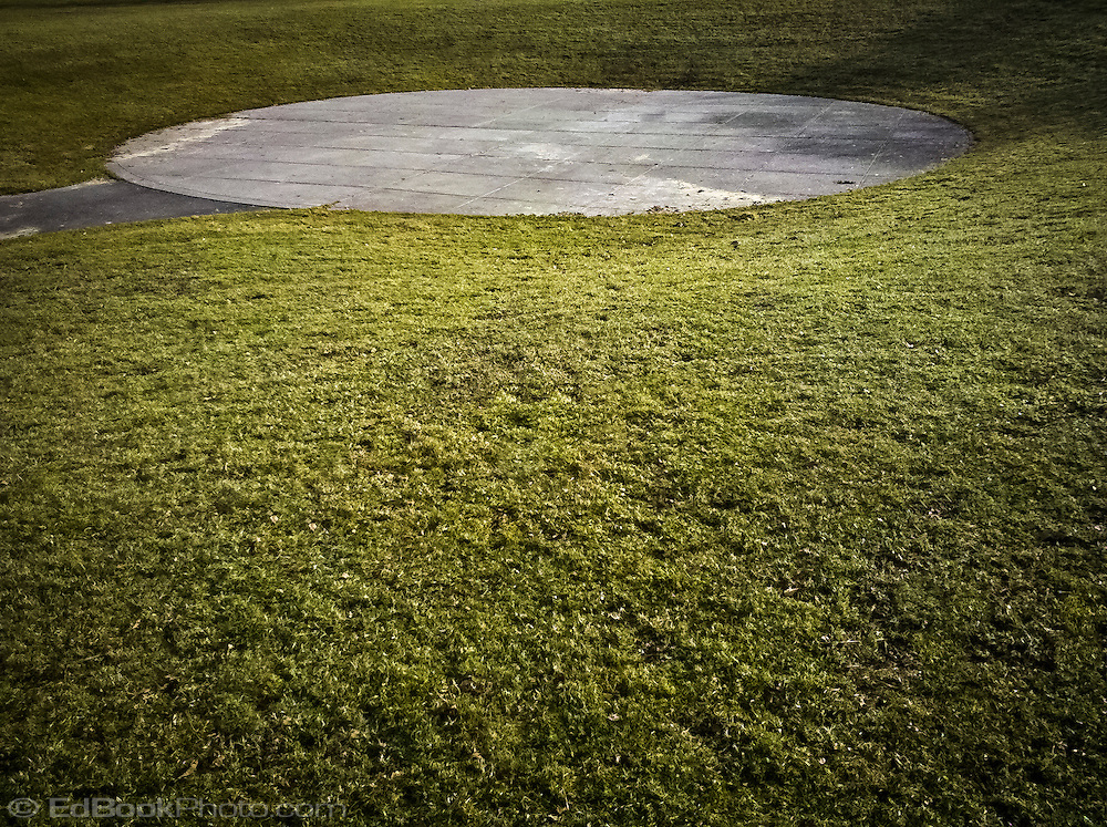 a small amphitheater formed by a concrete circle surrounded by a grassy bank at Evergreen Park in Bremerton, WA, USA