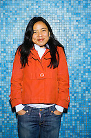An early 30's / late 20's Asian (Japanese/Filipino) woman with hands in pant pockets shrugging her shoulders and smiling in front of a wall of small torquoise tiles..Model Release: 20070513_MR_A