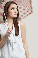 Beautiful young woman holding umbrella while looking away over gray background