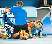 Rafael Nadal is tended to by a physical therapist during a medical time out on the court. Stanislaus Wawrinka of Switzerland defeated the number one player in the world R. Nadal of Spain to claim the 2014 Australian Open Men's Singles Championship. The Swiss won 6-3 6-2 3-6 6-3 in a match that will be remembered for a confusing and sometimes bizarre final three sets, with Nadal clearly hampered by a left lower back injury and seemingly on the verge of retirement in the second set.. The match was held on center court at Melbourne's Rod Laver Arena.