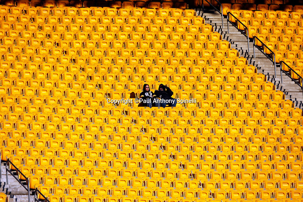 Pittsburgh Steelers fans sit in a sea of yellow seats as they arrive early for the NFL 2011 AFC Championship playoff football game against the New York Jets on Sunday, January 23, 2011 in Pittsburgh, Pennsylvania. The Steelers won the game 24-19. (©Paul Anthony Spinelli)