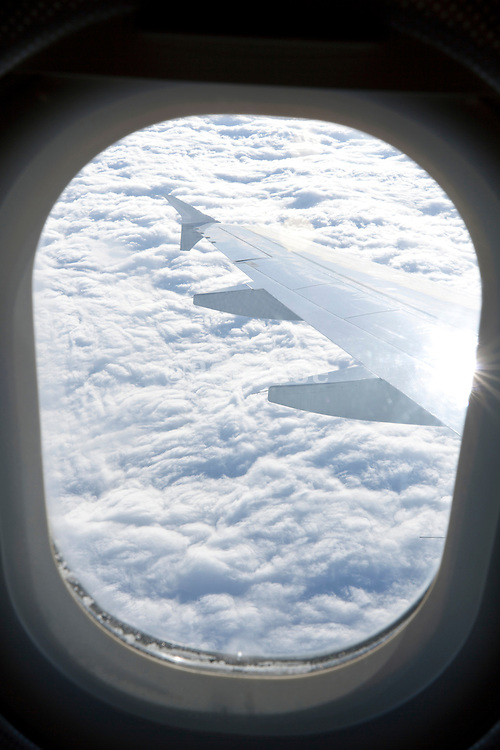 airplane making a turn while flying above the clouds