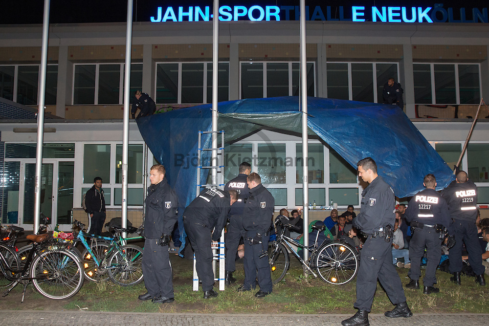 Berlin, Germany - 09.07.2016<br /> <br /> About 20 Syrian refugees stayed overnight after the closure of the refugee makeshift shelter in the Jahn Sport Hall in Berlin-Neukoelln front of the hall. Previously the Syrians got new sleeps allocated in the shelter at the former Tempelhof Airport. In protest against the many months lasting accommodation in mass makeshift camps where there is virtually no privacy, the refugees remained in front of the sports hall and spent the night there. With the help of a few dozen supporters they built a rain cover and built up some cots. Police officers demanded during the night that the cots and the rain cover to be removed.Those present did not follow the instruction, which is why some dozen policemen were approaching to seized the camp beds and the tarp. The mood at the police operation was completely peaceful, the refugees and their supporter were sitting on the ground and sang songs.<br /> <br /> <br /> Etwa 20 syrische Fluechtlinge uebernachteten nach der Raeumung der Notunterkunft in der Jahnsporthalle in Berlin-Neukoelln vor der Halle. Den Syrern wurden zuvor neue Schlafplaetze in der Sammelunterkunft im ehemaligen Flughafen Tempelhof zugewiesen. Aus Protest gegen die seit vielen Monaten anhaltende Unterbringung in Massenunterkuenften in denen es quasi keine Privatsphaere gibt blieben die Fluechtlinge vor der Sporthalle und verbrachten die Nacht dort. Mit Hilfe von einigen dutzend Unterstuetzern errichteten sie einen Regenschutz und bauten einige Feldbetten auf. Einsatzkraefte der Polizei verlangten im Laufe der Nacht, dass die Feldbetten und die Regenschutzplane entfernt werden, als die Anwesenden der Aufforderung nicht nachkamen rueckte die Polizei mit Verstaerkung an und beschlagnahmte einige Feldbetten und die Plane. Die Stimmung bei dem Polizeieinsatz war komplett friedlich, die Betroffenen sa&szlig;en dabei auf dem Boden und sangen Lieder. <br /> <br /> Photo: Bjoern Kietzmann