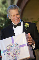 Middle-aged man in tuxedo holding present, portrait